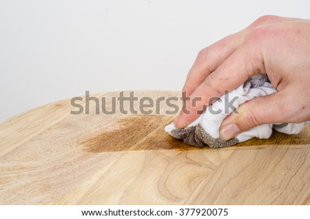 Applying a dark oak stain onto wood using a cloth. Landscape with copy space. - stock photo