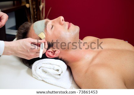 Applying a facial mask to a male customer - stock photo
