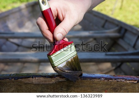Applying a pine tar on a wooden boat, to protect and preserve the wood. - stock photo