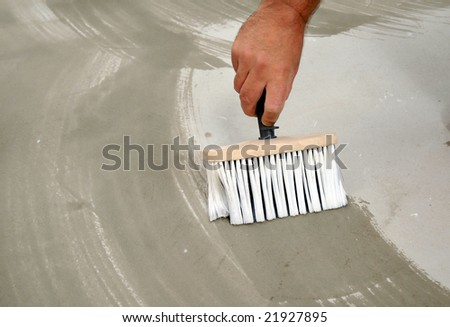 applying adhesive on the floor with a brush