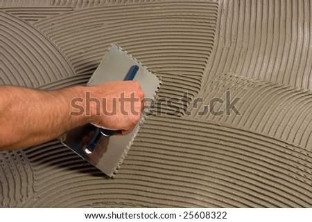 Applying adhesive with mason's float - stock photo