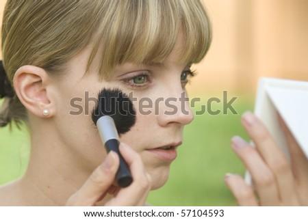 Applying blush with brush - stock photo