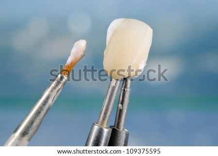 applying ceramic material on crown, dental technology - stock photo