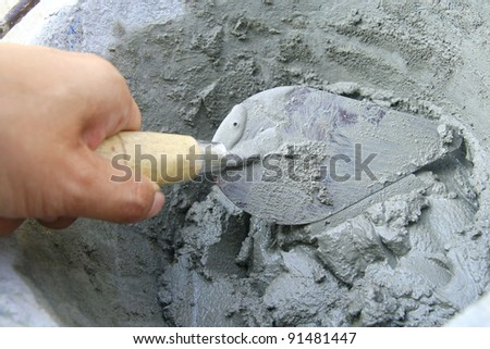 Applying construction trowel in wet cement - stock photo