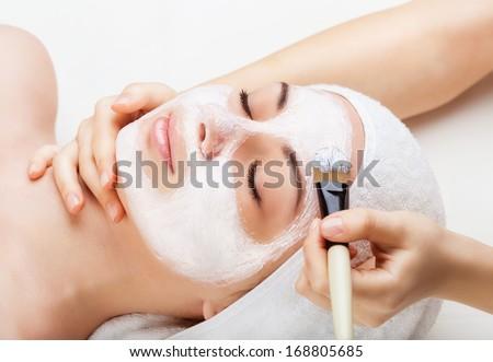 Applying facial mask at woman face at beauty salon - stock photo