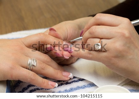 Applying gel at nail during professional manicure