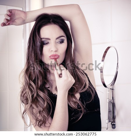Applying make up concept. Beautiful woman with red lipstick in front of mirror in bathroom. Indoor. - stock photo
