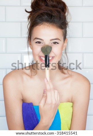 Applying make up concept, young attractive smiling woman covered with towel with cosmetic brush - stock photo
