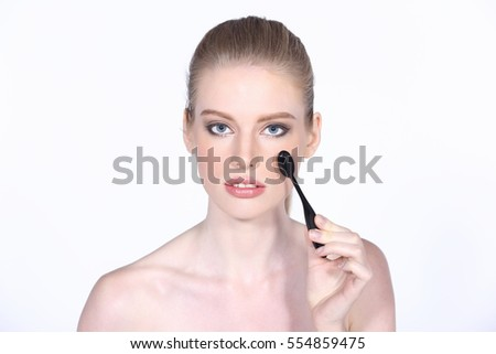 Applying make up foundation powder and brush for eyes. eye shadow for a young beautiful girl with cosmetic fine brush stick. close up, studio lighting gray background