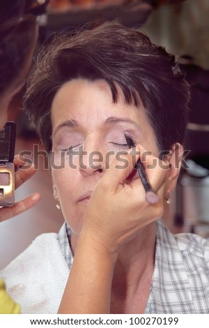 Applying make-up on a middle aged Hispanic female