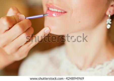 applying make up to brides lips - stock photo
