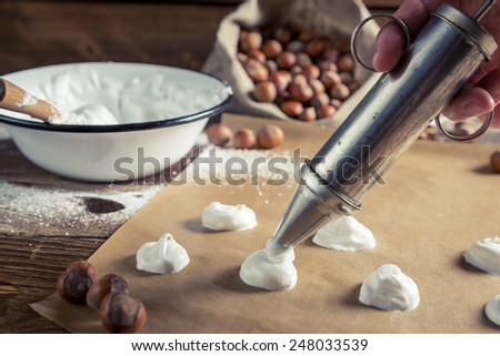 Applying meringues on baking paper for macaroons - stock photo