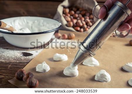Applying meringues on baking paper for macaroons - stock photo