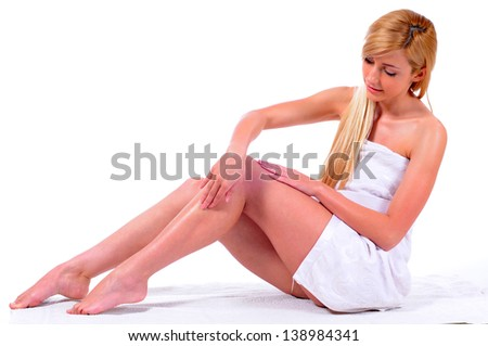 Applying moisturizer cream. Care for female legs isolated on white background - stock photo