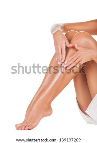 Applying moisturizer cream on the legs  isolated on white background - stock photo