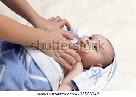 Applying moisturizing cream on face of baby after bath - stock photo
