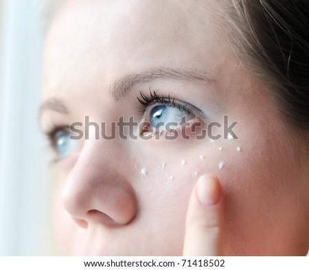 applying of cream under eye - soft selective focus - stock photo