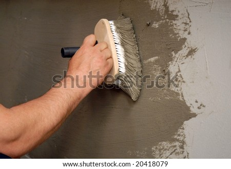 applying parget on the wall with a brush