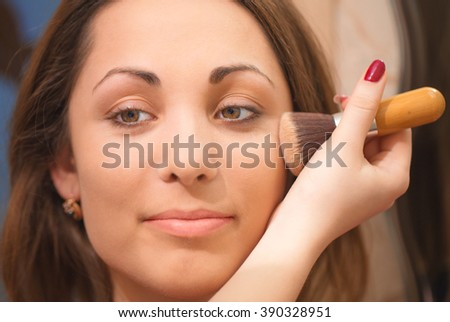 Applying powder on beautiful girl's face.