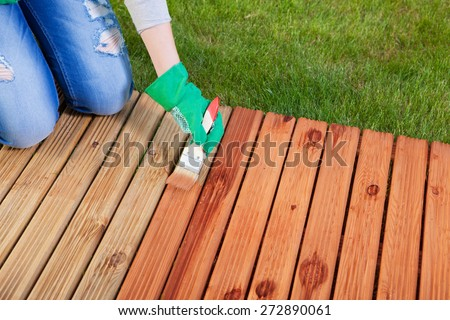 Applying protective varnish on a patio wooden floor, maintenance concept - stock photo