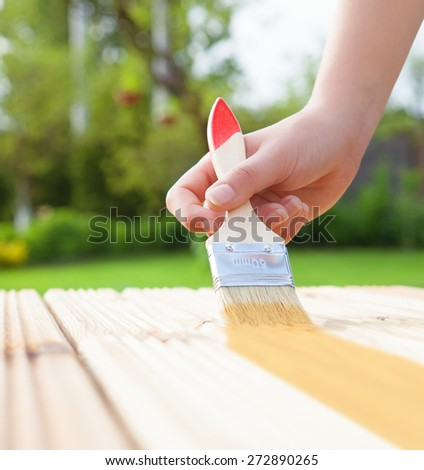 Applying protective varnish on a wooden furniture, diy house improvement concept - stock photo