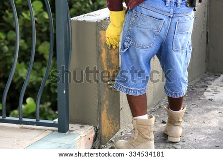 Applying stucco to a concrete block wall. - stock photo