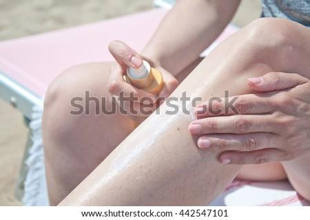 applying sunscreen on legs - stock photo