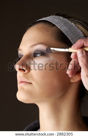 Applying the make up. - stock photo