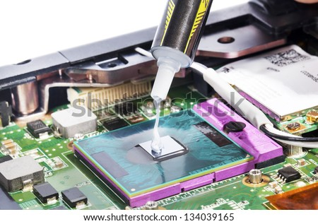 Applying thermal compound on video chip with syringe - stock photo