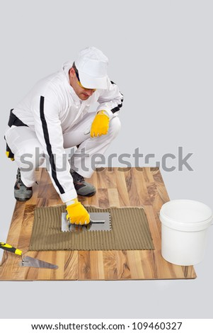 Applying Tile Adhesive with Notched Trowel on a old wood Floor