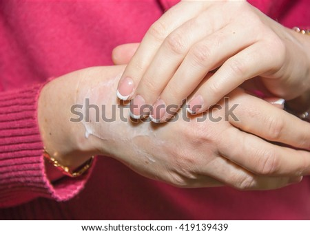 applying to the hands of cosmetic moisturizing cream, softening and skin treatment - stock photo