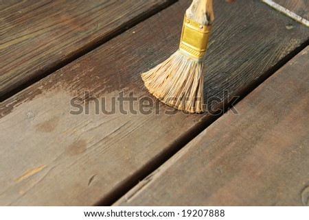 applying waterproofing oil to a wooden deck with a paintbrush