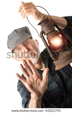 Apprehensive railroad man holding a glowing red lantern. - stock photo