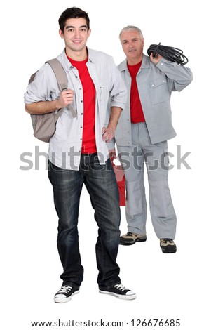 apprentice electrician and senior craftsman standing together - stock photo