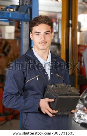 Apprentice Mechanic Holding Car Battery In Auto Repair Shop - stock photo