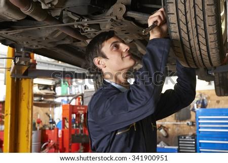 Apprentice Mechanic Working Under Car - stock photo