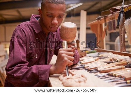 Apprentice Using Chisel To Carve Wood In Workshop - stock photo