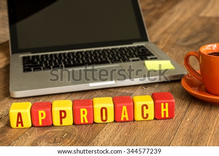 Approach written on a wooden cube in a office desk - stock photo