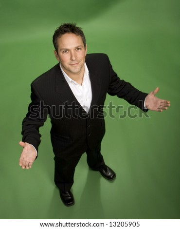 Approachable young business man with open arms isolated on a green screen - stock photo