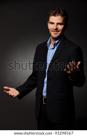 Approachable young business man with open arms  on ddark background - stock photo
