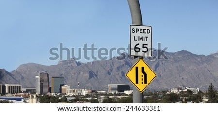 Approaching desert city of Tucson downtown with 65 miles per hour speed limit and narrow road ahead, Arizona, American Southwest - stock photo