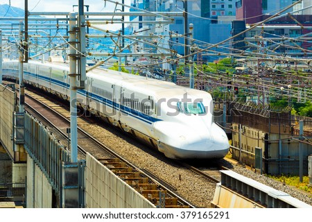 Approaching high speed train shaped like bullet on elevated rails surrounded by wires seen from above aerial view. Horizontal
