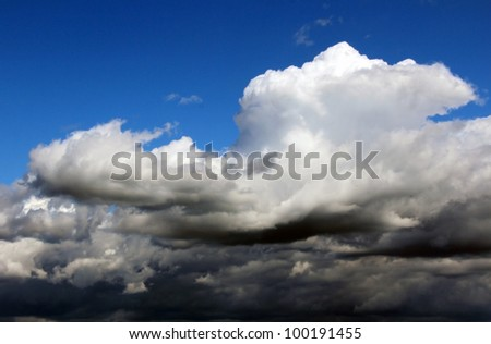 Approaching storm clouds against blue sky - stock photo