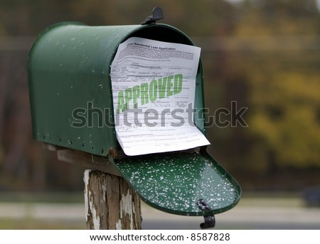 Approved residential loan application sticking out of mailbox.  All information is fictional. - stock photo