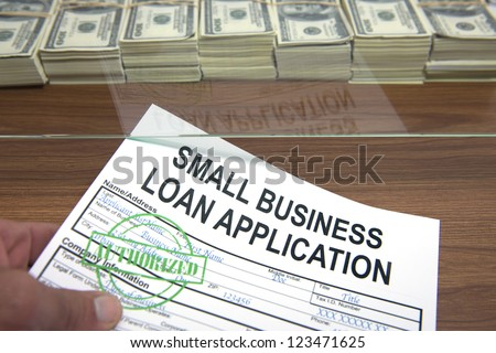 Approved small business loan application and dollar bills - stock photo