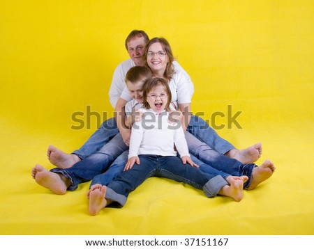 appy young family on floor with mother, father, daughter and son - yellow background