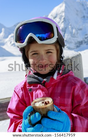 Apres ski, skiing, winter, child - young skier drinking hot chocolate  in winter resort - stock photo