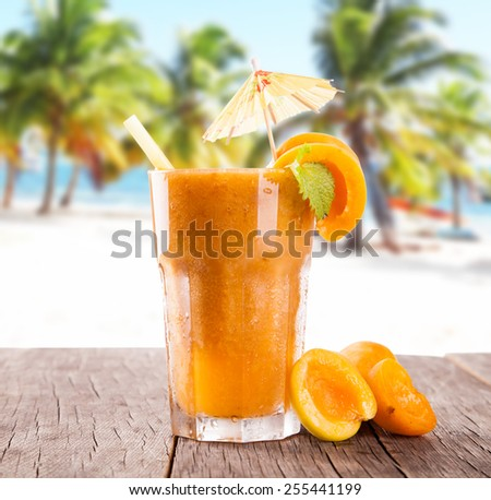Apricot cocktail on wooden table with beach background, summer concept, fresh fruits - stock photo