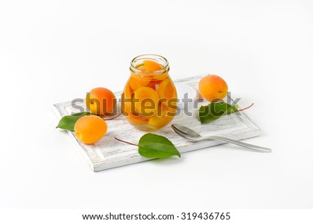 apricot compote in the glass jar standing on the wooden cutting board and surrounded by fresh apricots and leaves - stock photo