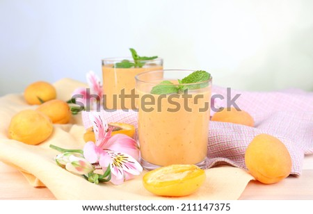 Apricot dessert in glasses on table on bright background